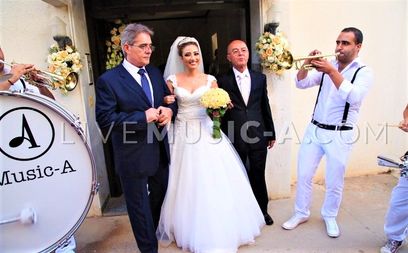 Bride leaving parents house while musicians playing